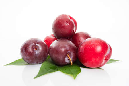 plums with plum leaves on a white background