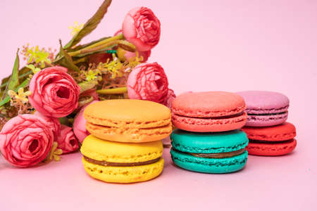 Macarons with tender small roses. Sweets and desserts concept of macaroons Banco de Imagens