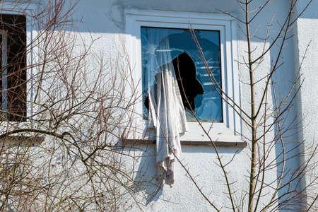 Broken window in a  building. The concept of vandalism