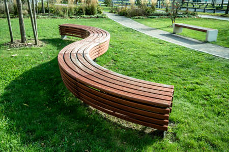 A modern bench  in a city park on a sunny day