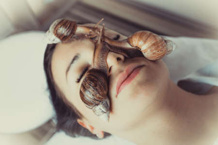 Portrait of young woman with a snails achatina on her face 写真素材