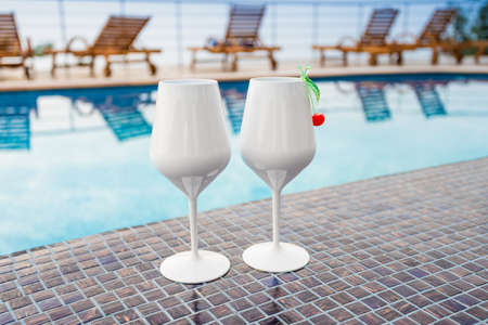 Two Cocktails near the Swimming Pool on the Background. Exotic Summer Vacation
