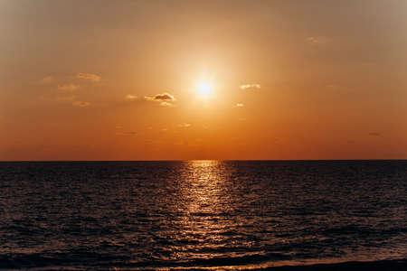 Prachtige zonsondergang boven de zee. Weerspiegeling van de zonsondergang in het water.
