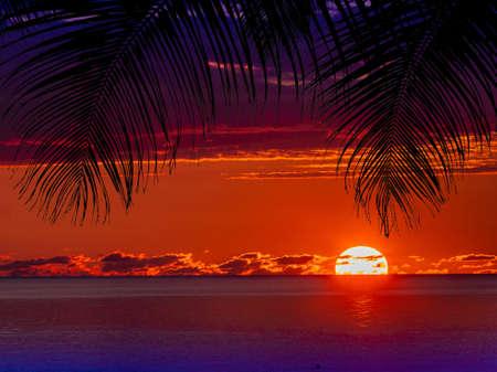 Roter Wolkensonnenuntergang, der im Wasser reflektiert