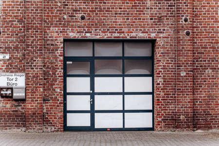Large garage door with brick wall and asphalt driveway