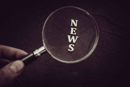 Focus on News.  News Word Magnifying Glass on black background