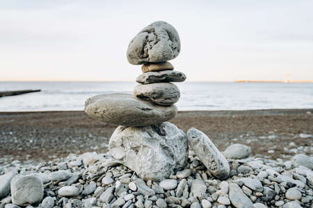 The figure of stones standing on each other, on the beach against the sea. Reklamní fotografie