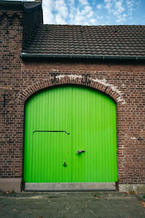 Large bright green wooden doors in an old brick building. Doors in a renovated building.