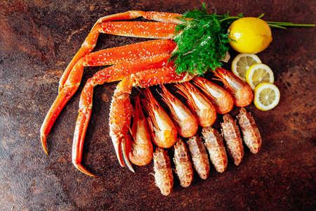 Composition with crab, shrimp, herbs and lemon on a red background Reklamní fotografie
