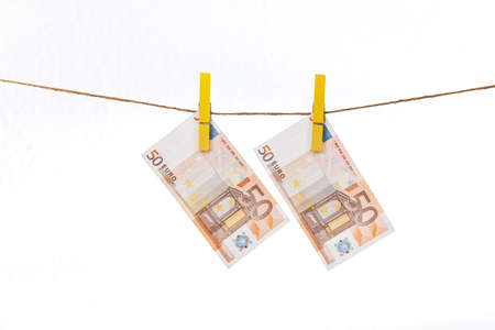 Euro banknotes are attached with yellow clothespins to a rope on a white background Фото со стока