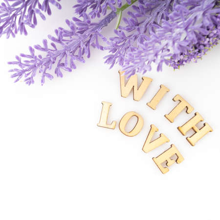 Sign of love with a bunch. Purple flowers petals love text