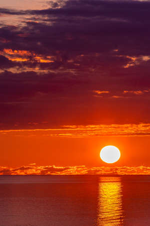 Panorama of sun in dark clouds and sea water surface at sunset