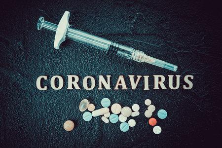 Coronavirus vaccine vial with injection syringe isolated on black background