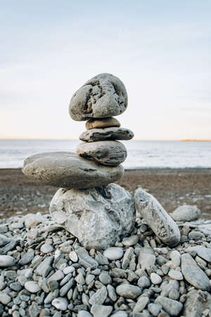 The figure of stones standing on each other, on the beach against the sea. 免版税图像