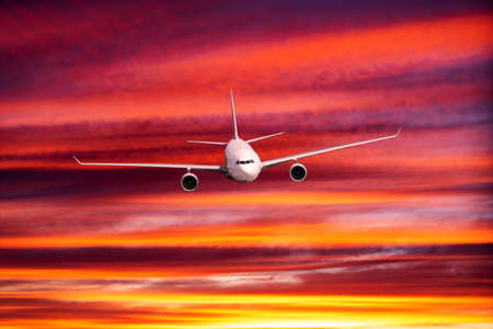 Passengers commercial airplane flying above clouds in sunset light. 免版税图像