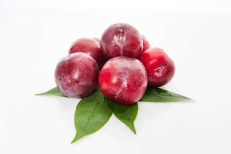 plums with plum leaves isolated on a white background 免版税图像