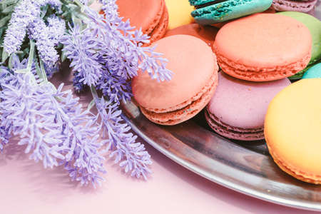 tasty colorful macarons on pink background