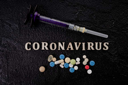 Coronavirus vaccine vial with injection syringe isolated on black background 免版税图像 - 161235315