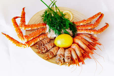 Red king crab and shrimp on a plate with lemon and dill. White background