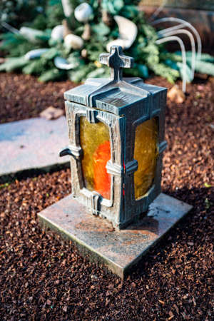 damaged grave light with burning candle on a grave
