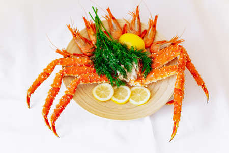 Red king crab and shrimp on a plate with lemon and dill. White background 免版税图像 - 161235412
