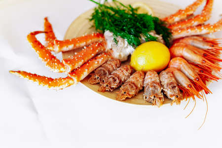 Red king crab and shrimp on a plate with lemon and dill. White background 免版税图像 - 161235520