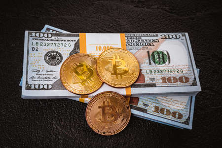 golden bitcoin metal coin on one US dollar bill