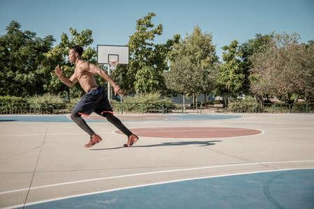 Un jeune homme afro-américain sans t-shirt saute sur un terrain de basket dans un parc de Madrid pendant l'été à midi. Il fait un saut génial pour courir.