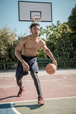 One afroamerican young man without tshirt is playing basketball in a park in Madrid during summer at midday. He is bouncing the ball under the basket.