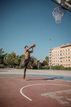 One afroamerican young man without tshirt is playing basketball in a park in Madrid during summer at midday. He is doing an awesome jump to make a dunk and put the ball into the basket.