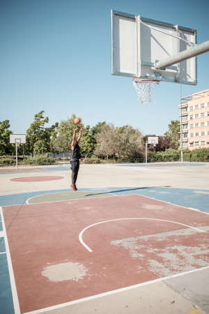 One afroamerican young man is playing basketball in a park in Madrid during summer at midday. He is shooting the ball to the basket from half distance. Stock Photo