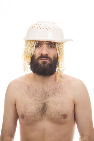 Bearded, funny, young man with colander and spaghetti on his head. White background. Body without clothing. Portrait photo. Caucasian guy.