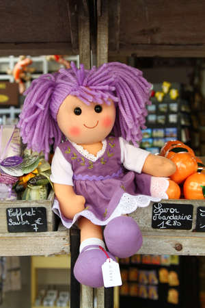 Doll with lavender color hair and dress in market in city Menton on French riviera Stock fotó