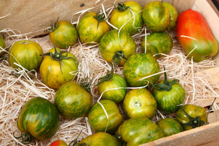 menton: Green tomatoes in wooden box at market in Menton, town in South France, French riviera