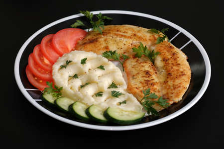 Fried tilapia fish fillets on plate with mashed potatoes, cucumber, tomatoes, parsley. Stok Fotoğraf - 78153299