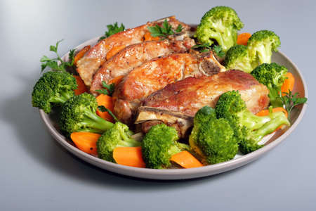 Country style baked in oven pork ribs on plate with broccoli and carrots