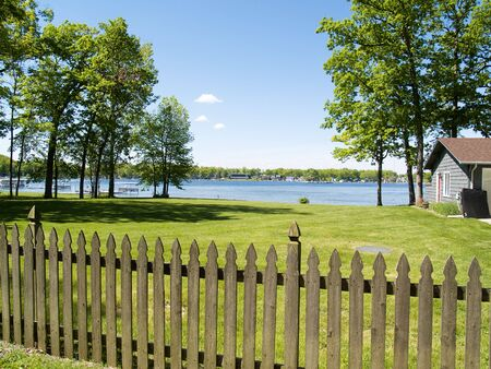 A picket fence, overlooking a body of water. Taken from a vacation spot.