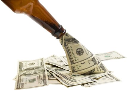 Cash being poured from a glass bottle, isolated on white.