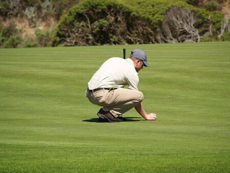 A golfer aligns his putt on the green, holding his ball and a putter.