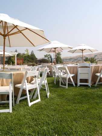 Tables,  chairs, and umbrellas arranged and ready for an outdoor party.