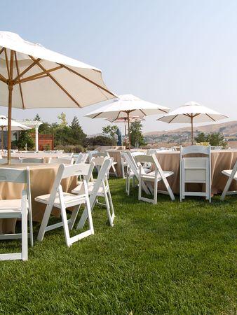 Tische, Stühle, Sonnenschirme und organisiert und bereit für eine Party im Freien.