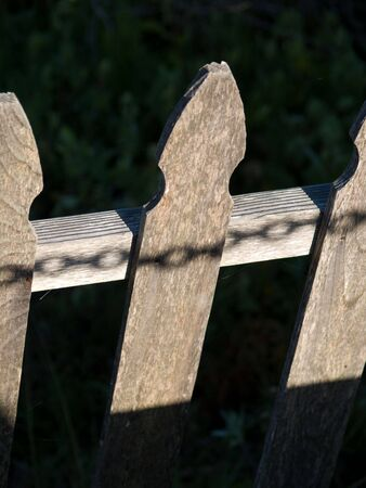 Shadow of a chain on a wooden fence, symbolizing captivity. Stock fotó