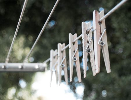 Shallow depth of field, several clothespins on the line outside.