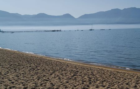Lake shore with boats and pier in the background, mountains and fog in the distance. Stock fotó