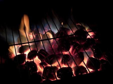 Long exposures of coals buring underneath a grill. Stock fotó