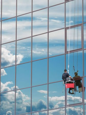 cleaning an office: Window washer at work and reflect the sky in the windows