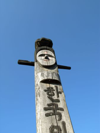 Smiling wooden idol on the background of blue sky