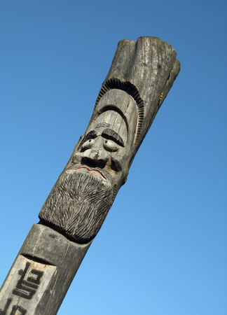 Wooden idol on the background of blue sky