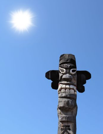 Wooden idol on the background of blue sky photo