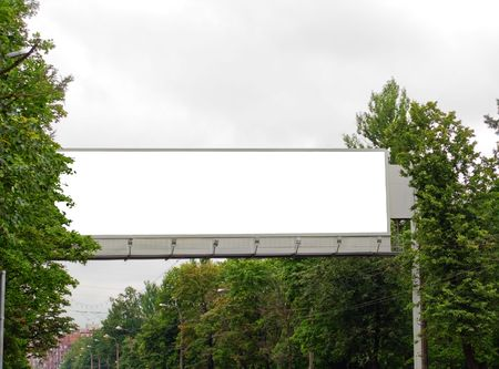 The superbig billboard among trees over the main street Stock Photo
